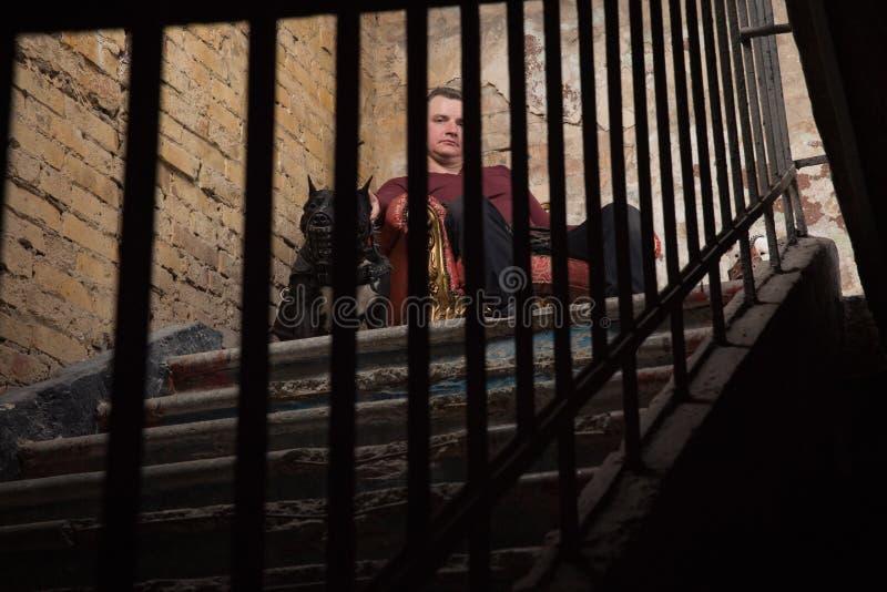 Uomo adulto che satting in una poltrona d'annata sui precedenti di una parete sbucciata Da ogni lato l'uomo che si siede due cani fotografie stock libere da diritti
