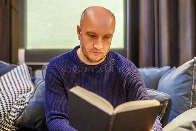 Uomo adulto che si siede sullo strato e che legge un libro fotografia stock