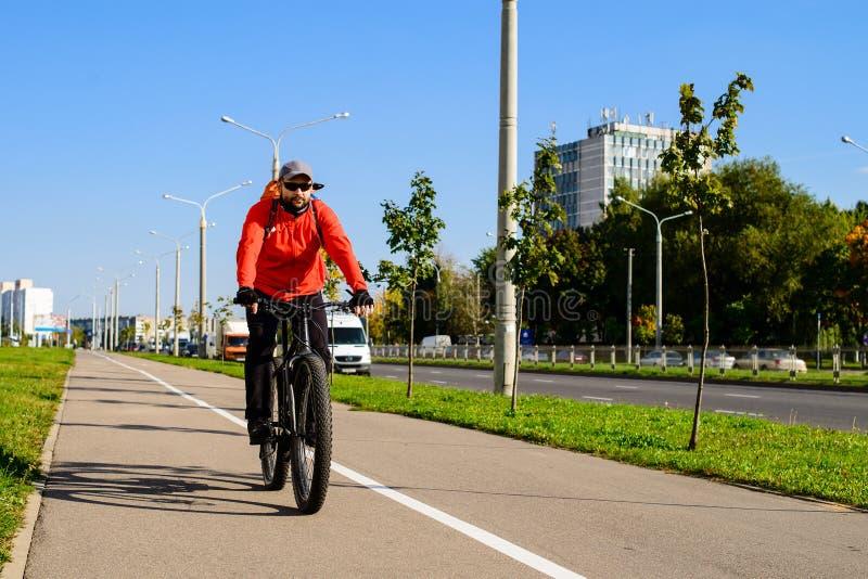 Uomo adulto con lo zaino che guida una bicicletta nella via della città Automobile immagine stock
