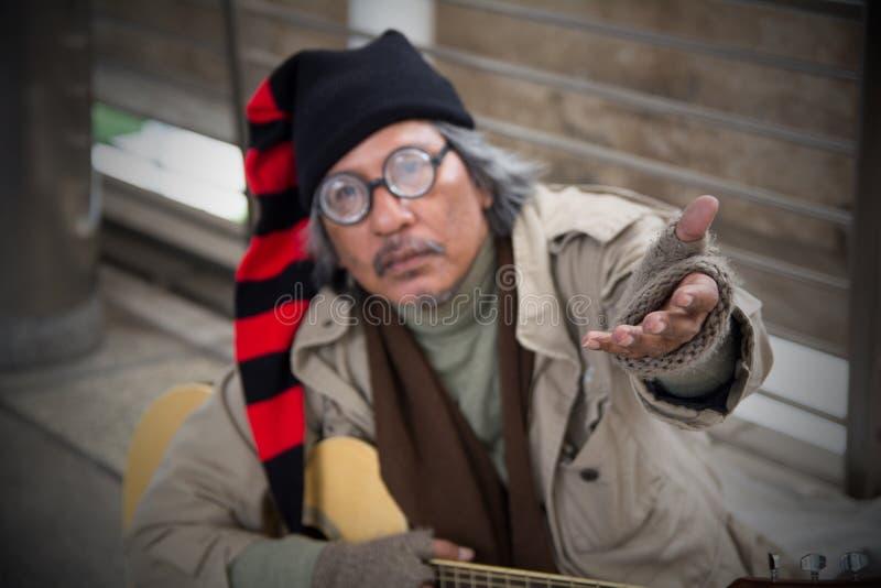 Uomo adulto senior senza tetto che si siede e che elemosina in passaggio fotografia stock libera da diritti