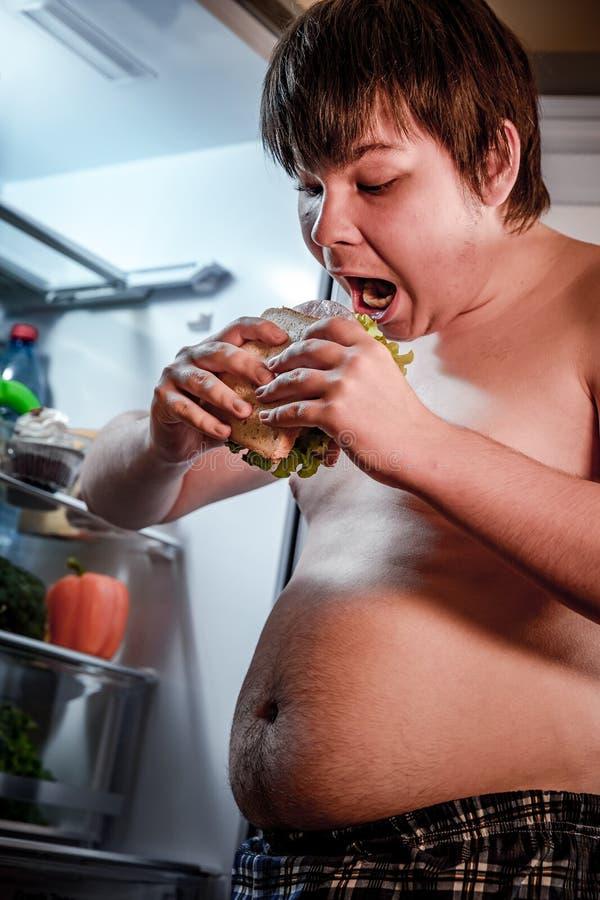 Uomo affamato che tiene un panino nelle sue mani e condizione accanto a fotografia stock libera da diritti