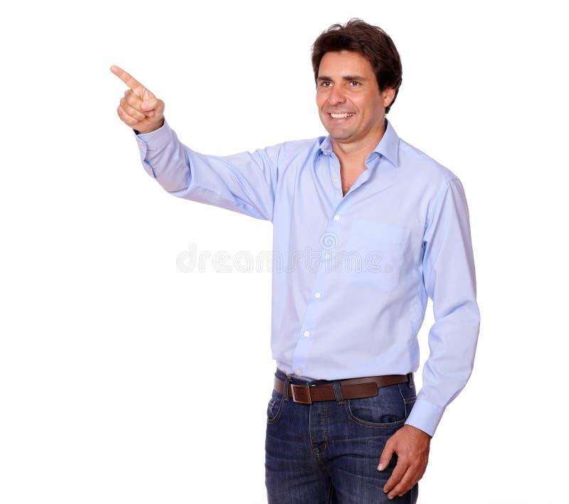 Uomo affascinante che indica la sua destra mentre stando immagine stock libera da diritti