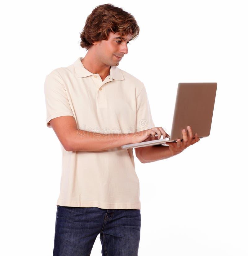 Uomo affascinante che lavora al computer portatile mentre stando fotografie stock
