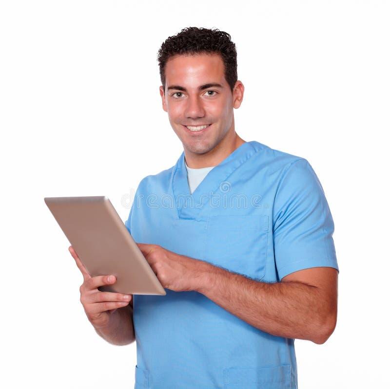 Uomo affascinante dell'infermiere che per mezzo del suo pc della compressa immagini stock libere da diritti