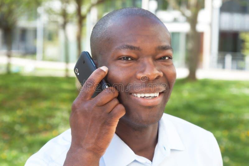 Uomo africano alla macchina fotografica di sguardo esterna del telefono immagini stock