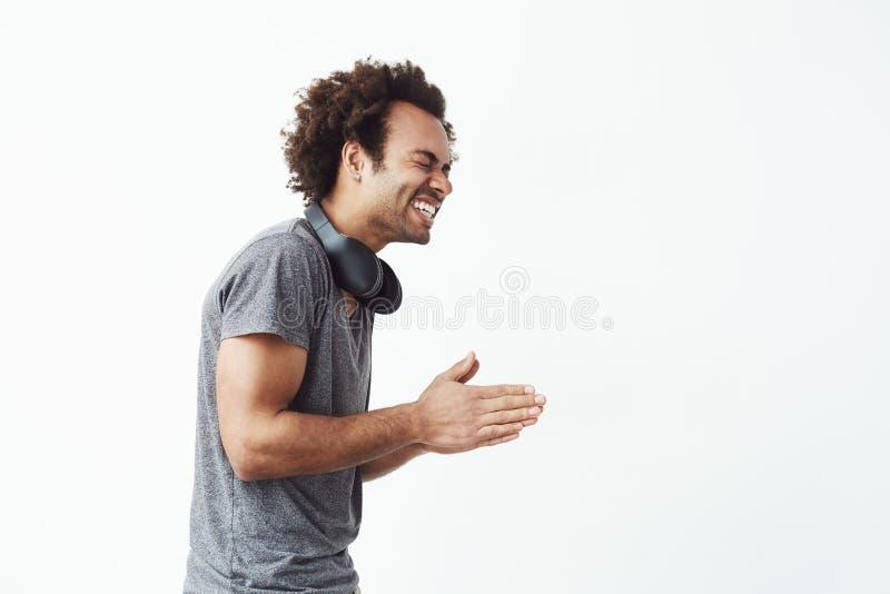 Uomo africano allegro con le cuffie che ride stare nel profilo sopra fondo bianco immagine stock libera da diritti