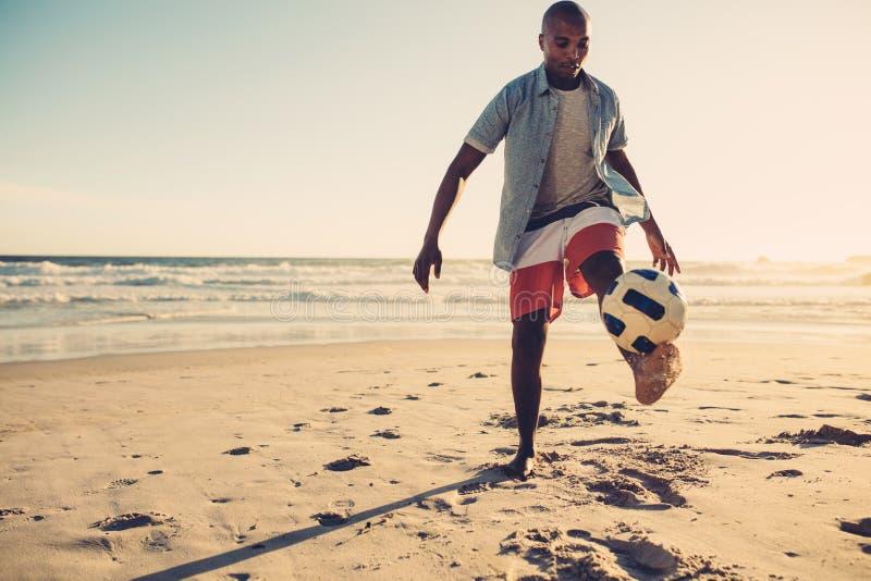 Uomo africano che gioca con il pallone da calcio alla spiaggia fotografia stock libera da diritti