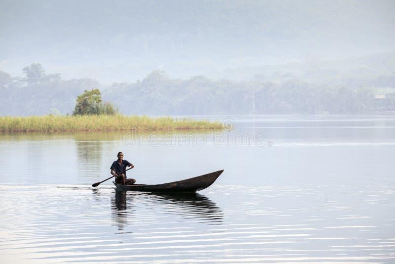 Uomo africano che guida una canoa immagine stock
