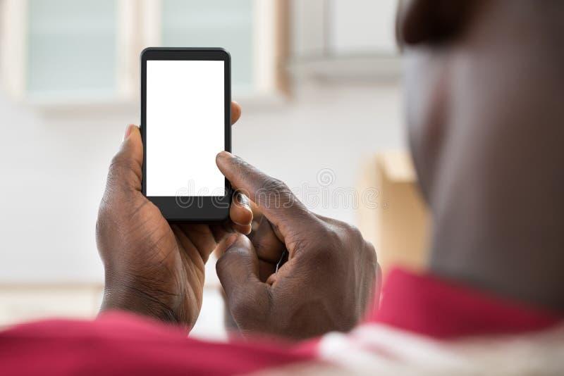 Uomo africano che per mezzo del cellulare immagini stock
