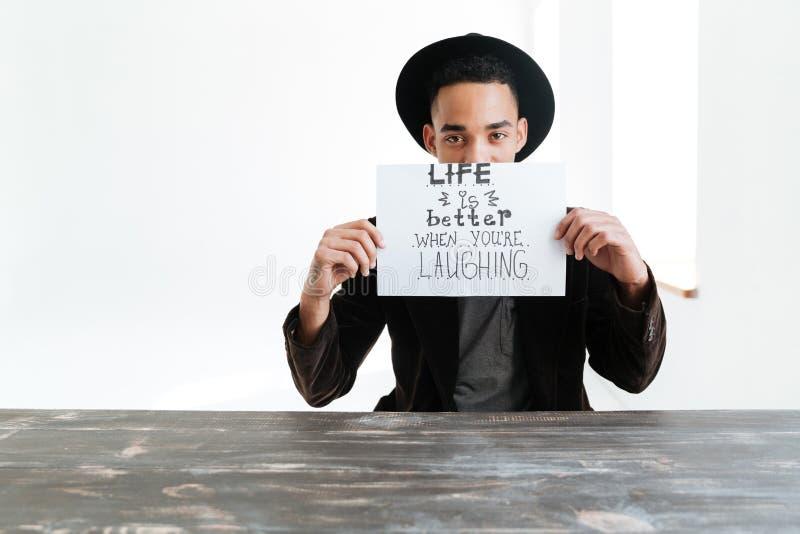 Uomo africano che si nasconde dietro il foglio di carta con le parole immagine stock