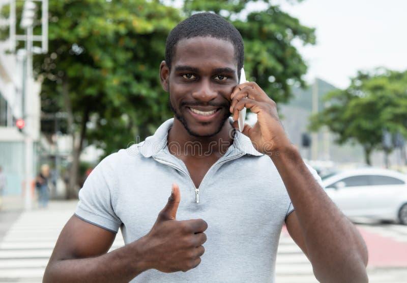 Uomo africano con la barba al telefono che mostra pollice su fotografie stock