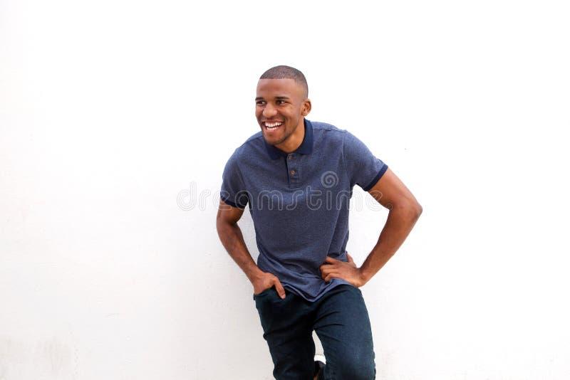 Uomo africano di risata che sta contro il fondo bianco immagine stock