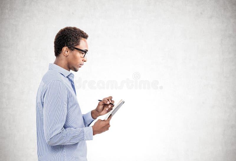 Uomo africano serio che prende le note, false immagini stock