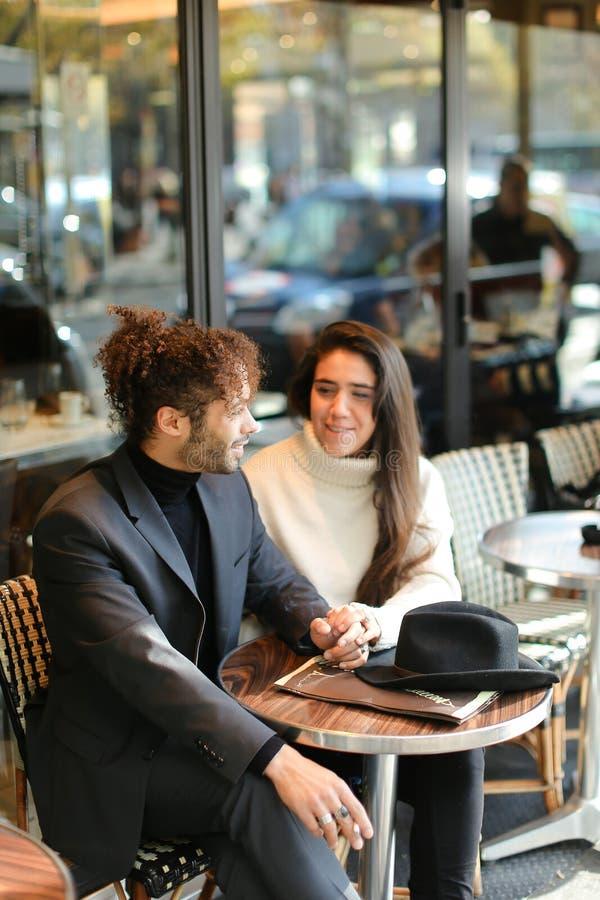 Uomo afro - americano e donna caucasica seduti al bar e parlano immagine stock