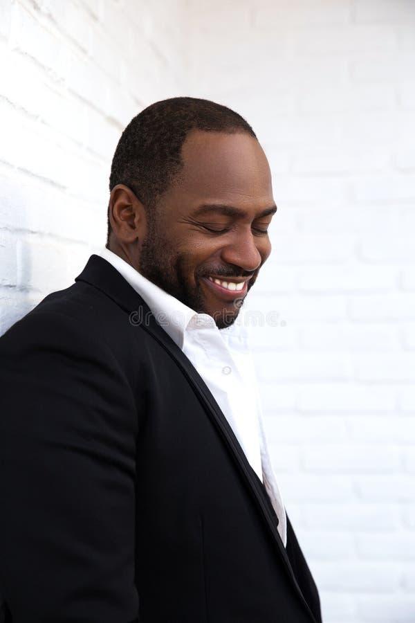Uomo afroamericano allegro bello in vestito nero di classe fotografia stock