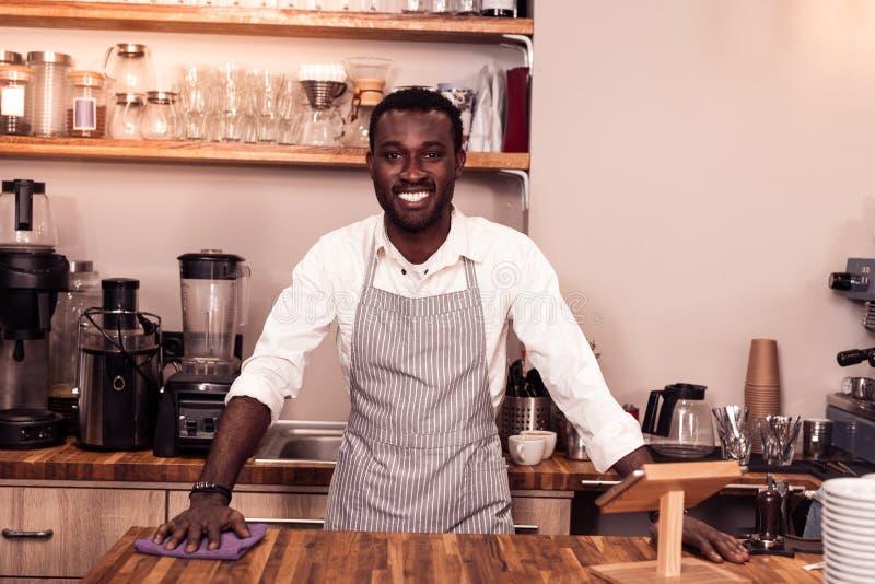 Uomo afroamericano allegro che è sul lavoro immagini stock