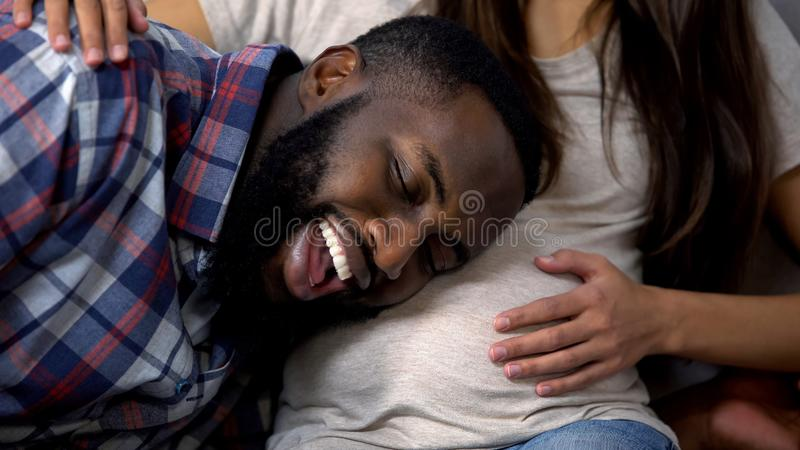 Uomo afroamericano allegro che ascolta il bambino in pancia, aspettativa felice, famiglia immagini stock