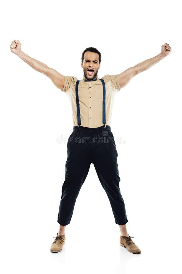 Uomo afroamericano allegro che dura in bretelle e farfallino che urlano e che celebrano successo fotografia stock