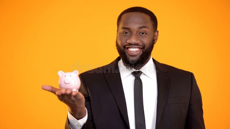 Uomo afroamericano allegro in vestito che mette moneta nel risparmio di pensionamento del porcellino salvadanaio immagine stock libera da diritti