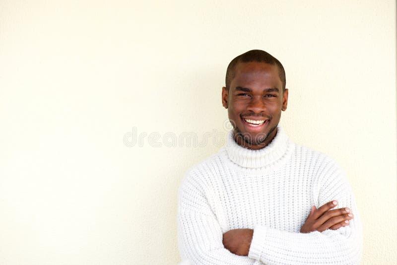 Uomo afroamericano bello che sorride con le armi attraversate contro fondo leggero fotografia stock libera da diritti