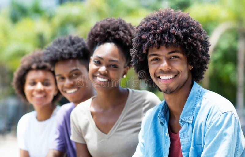 Uomo afroamericano bello con il gruppo di giovani adulti nella linea fotografie stock libere da diritti