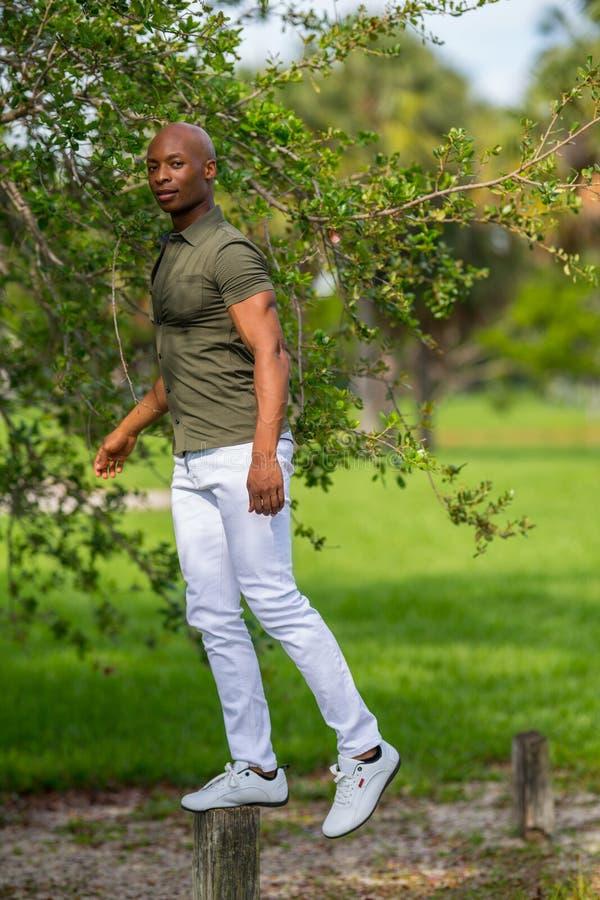 Uomo afroamericano bello di immagine giovane che equilibra su una posta di forma fisica nel parco immagini stock