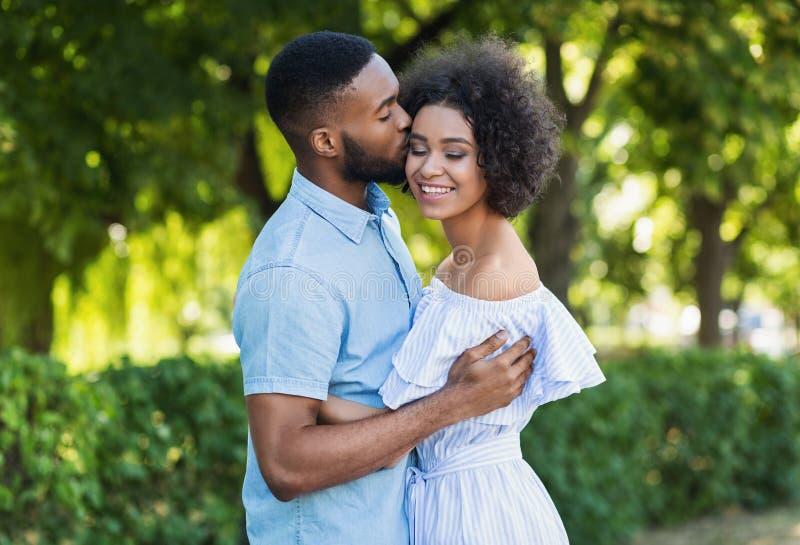 Uomo afroamericano che bacia la sua amica mentre camminando fotografie stock libere da diritti