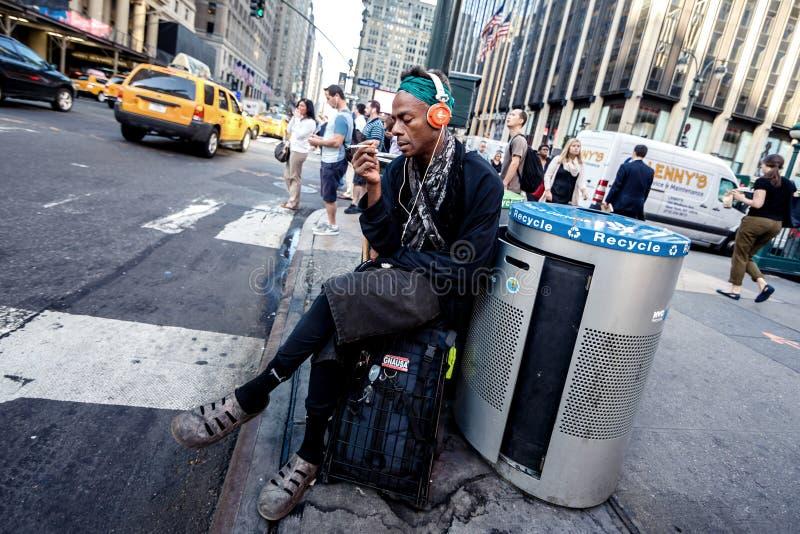 Uomo afroamericano che riposa vicino alla strada fotografia stock