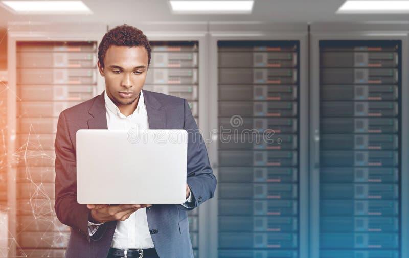 Uomo afroamericano con il computer portatile in una stanza del server fotografie stock libere da diritti