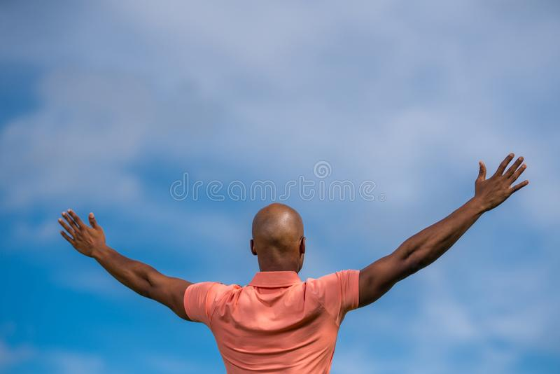 Uomo afroamericano del ritratto che affronta a partire dalla macchina fotografica con le armi aperte verso cielo blu immagine stock libera da diritti