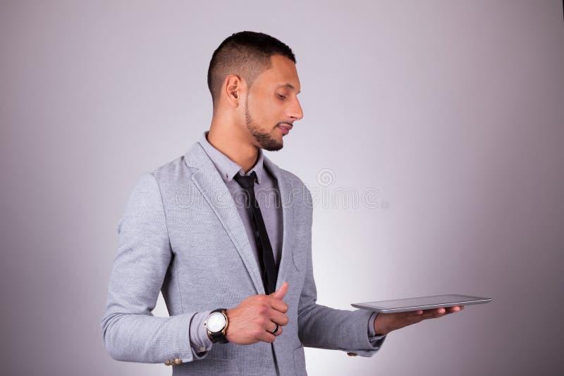 Uomo afroamericano di affari che per mezzo di una compressa tattile - peo nero fotografie stock libere da diritti