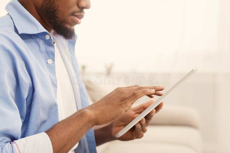 Uomo afroamericano facendo uso della compressa digitale a casa fotografia stock libera da diritti