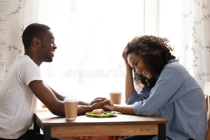 Uomo afroamericano felice alla data con l'amica attraente in caffè immagini stock