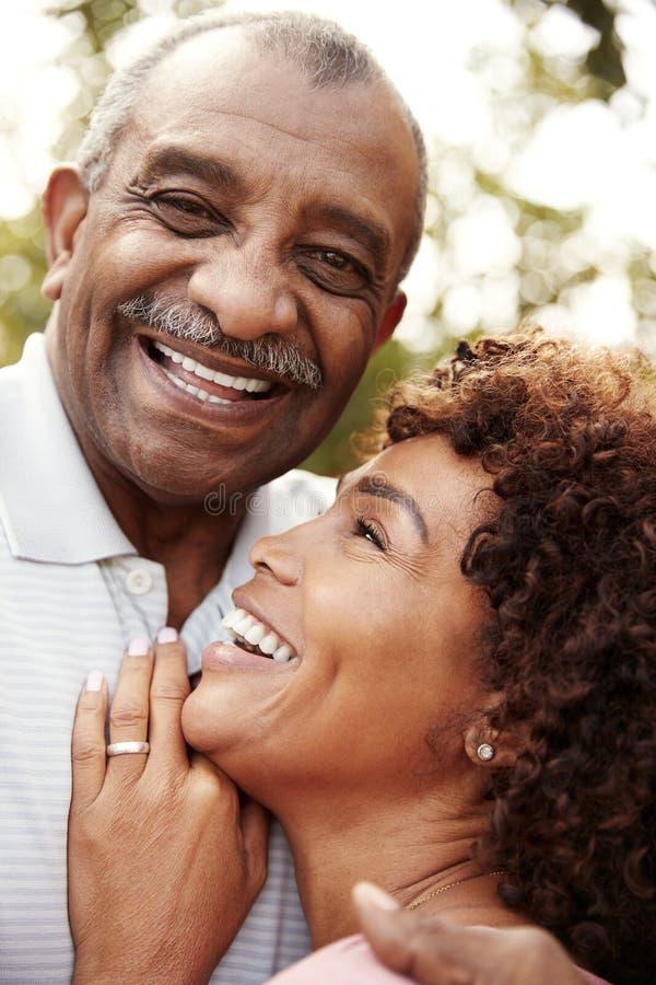 Uomo afroamericano senior e sua la figlia invecchiata middled che abbracciano e che ridono, verticali fotografie stock libere da diritti