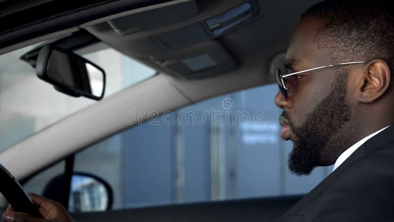 Uomo afroamericano serio che conduce automobile, esaminante attentamente la strada immagine stock libera da diritti