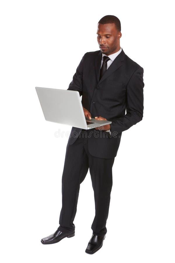 Uomo afroamericano sicuro di affari sul computer portatile fotografie stock