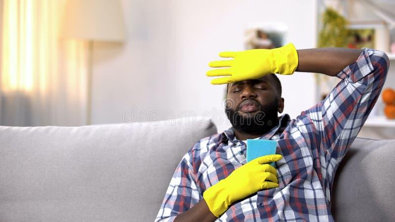 Uomo afroamericano stanco in guanti che si siedono sul sofà, rilassantesi dopo la pulizia della casa fotografia stock libera da diritti