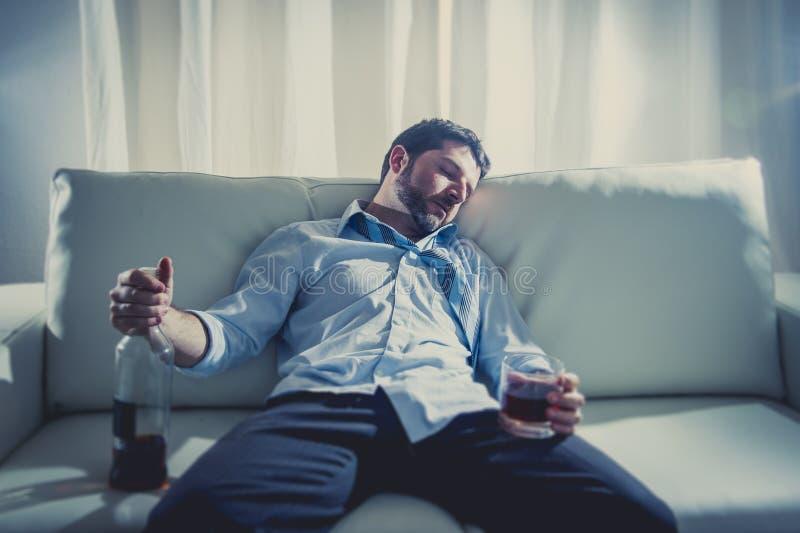 Uomo alcolico di affari nel sonno sciolto blu del legame potabile con la bottiglia di whiskey sullo strato immagini stock