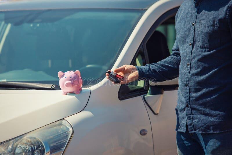 Uomo all'aperto che tiene le sue nuove chiavi dell'automobile e banca rosa dei soldi di porcellino sul cappuccio Successo economi immagini stock