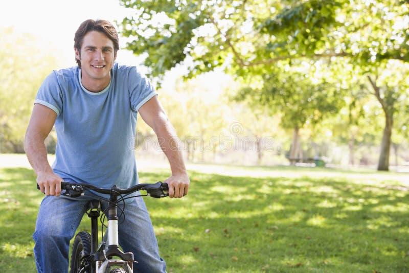 Uomo all'aperto sul sorridere della bici immagine stock