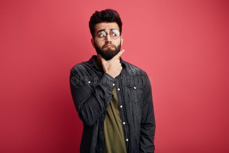 Uomo alla moda barbuto attraente serio che tocca mento e che esamina da parte la macchina fotografica fotografia stock