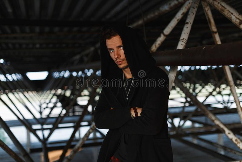 Uomo alla moda bello in abiti alla moda con un cappuccio vicino fotografia stock