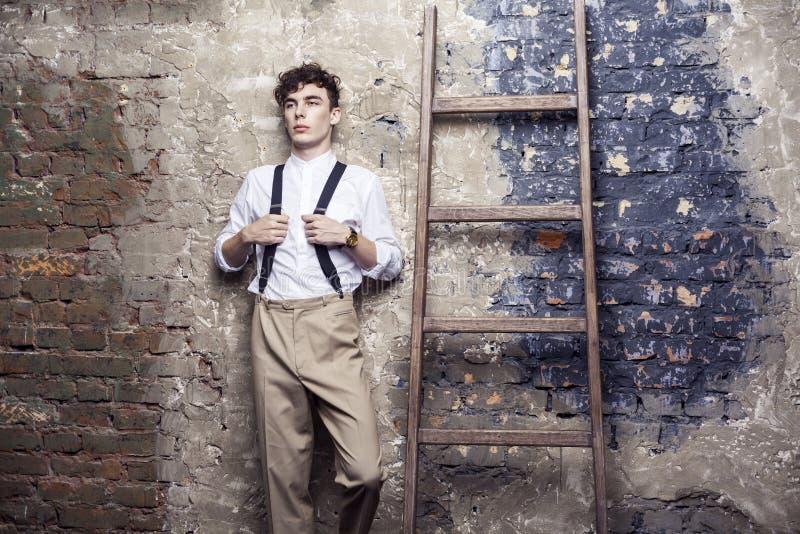 Uomo alla moda in camicia bianca e pantaloni beige che tengono le bretelle che posano e appoggiarsi vecchia scala di legno sul fo fotografia stock libera da diritti