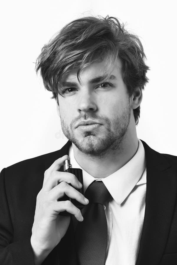 Uomo alla moda caucasico di affari con i baffi in vestito nero elegante ed in legame rosso che posano con il profumo in studio is fotografia stock