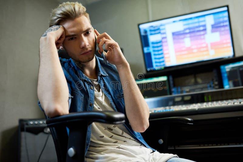 Uomo alla moda che parla sul telefono in studio immagini stock