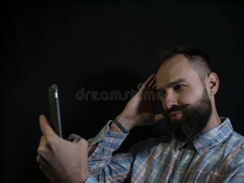 Uomo alla moda con una barba ed i baffi che posano e che prendono un selfie sul telefono su un fondo nero immagini stock libere da diritti