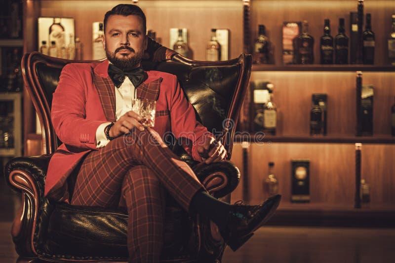 Uomo alla moda esagerato con il vetro del whiskey che si siede sulla poltrona dentro immagini stock libere da diritti