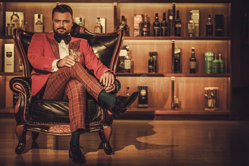 Uomo alla moda esagerato con il vetro del whiskey che si siede sulla poltrona dentro fotografia stock