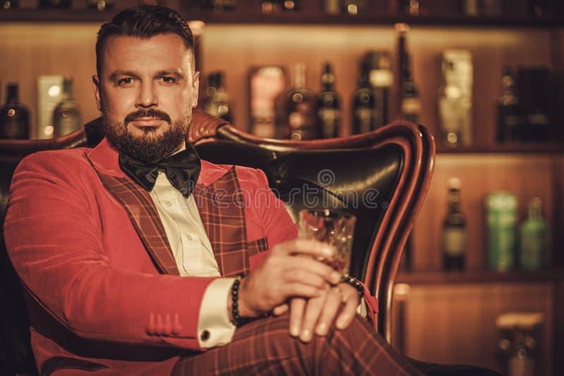Uomo alla moda esagerato con il vetro del whiskey che si siede sulla poltrona dentro immagini stock