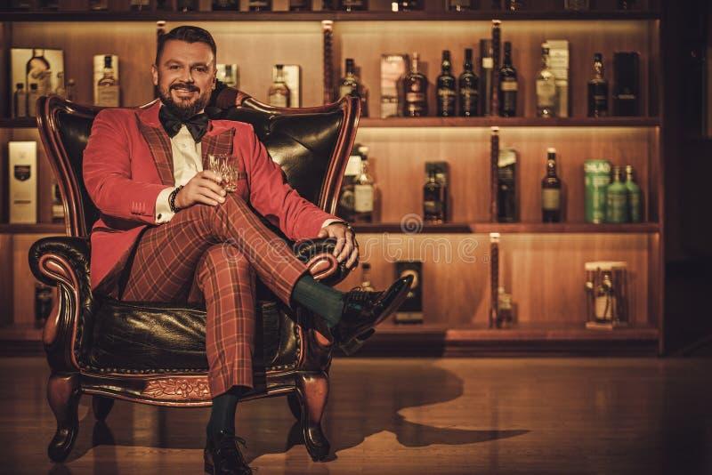 Uomo alla moda esagerato con il vetro del whiskey che si siede sulla poltrona dentro fotografie stock